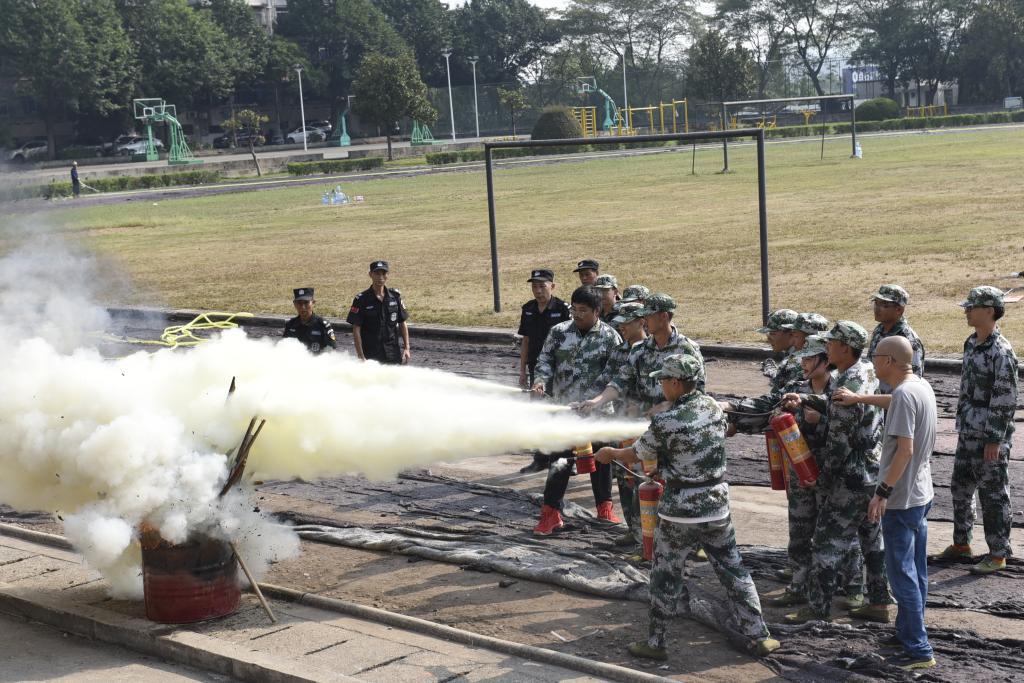 学生们体验使用灭火器灭火的过程
